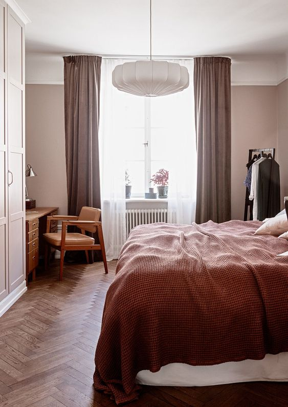 a mauve bedroom with mid-century modern furniture, mauve curtains, burgundy bedding and a paper lamp