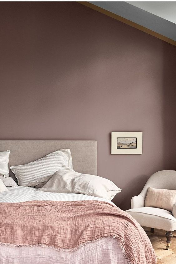 a mauve bedroom with neutral furniture, a pink blanket and neutral bedding and bold artworks