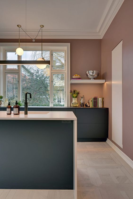 a mauve kitchen with graphite grey cabinets, white and black countertops, pendant lamps and a large window