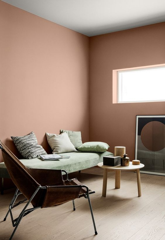 a mauve living room with a green daybed, a leather chair, a round wooden table and a catchy artwork