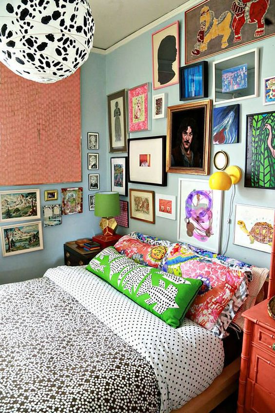 a maximalist gallery wall in various bright colors, with mismatching frames taking two walls looks very bold and cool