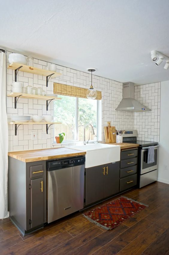 a mid century modern grey kitchen with open shelves, a white tile backsplash and butcherblock countertops is a chic space