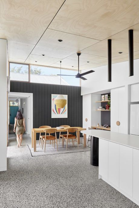 a mid-century modern kitchen and dining zone with chic furniture, clerestory windows for more light and cool pendant lights