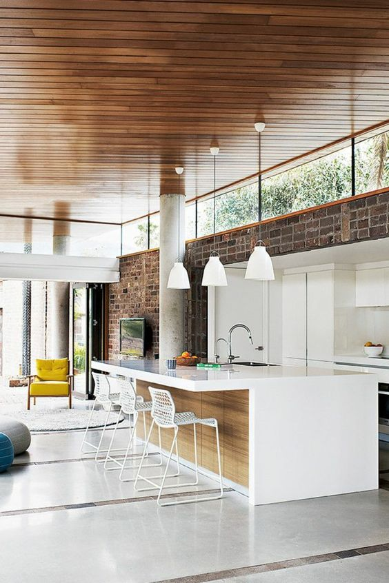 a mid-century modern kitchen with a brick wall, white minimalist cabinetry and clerestory windows that bring in light