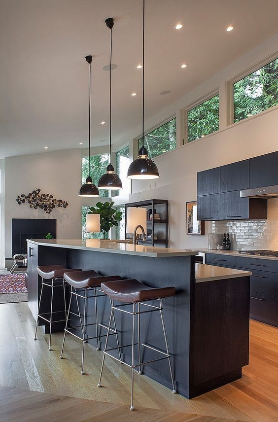 a mid-century modern kitchen with black cabinetry, clerestory windows for more light, pendant lamps and leather chairs