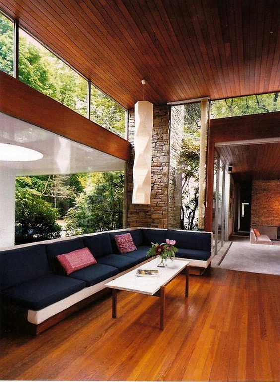 a mid-century modern living room with a large sectional, a coffee table and clerestory windows and a glazed wall