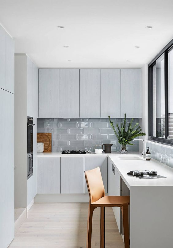 a minimal Nordic L-shaped kitchen with glass tiles and a window with a view is a lovely idea