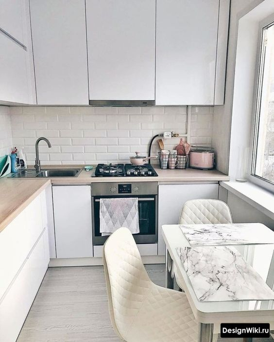 a minimalist L-shaped kitchen with sleek cabinetry and butcherblock countertops plus a small meal zone