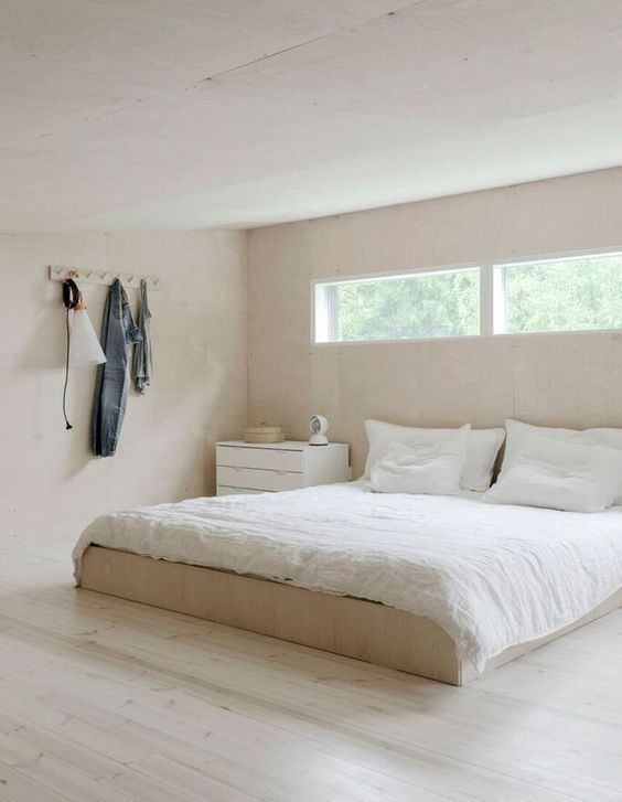 a minimalist bedroom in light shades, with a dresser and a bed plus clerestory windows for more light