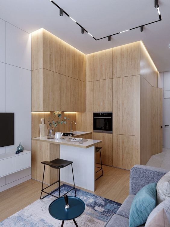 a minimalist blonde wood L-shaped kitchen with built-in lights and a tiny kitchen island is super cool