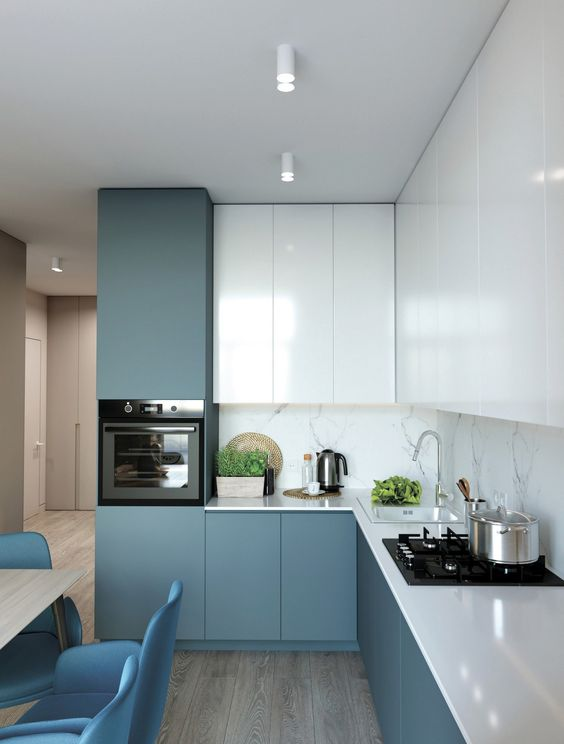 a minimalist blue and white kitchen with a white stone backsplash and white countertops is all chic