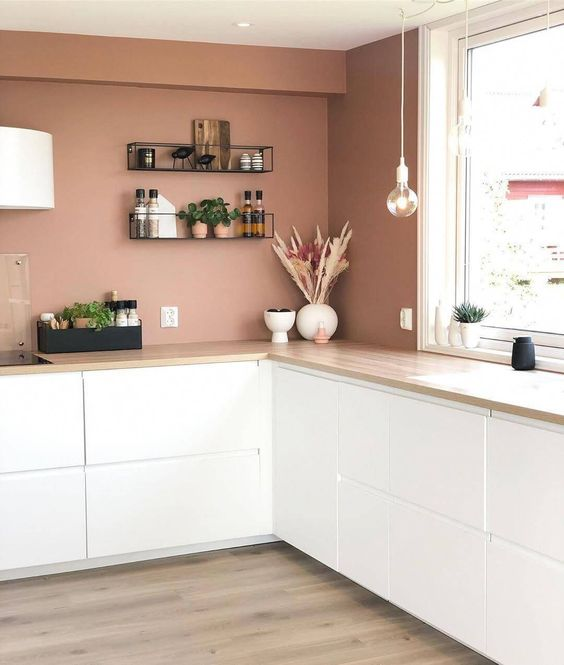 a minimalist mauve kitchen with only lower white cabinets, pendant bulbs, open shelves and white lamps