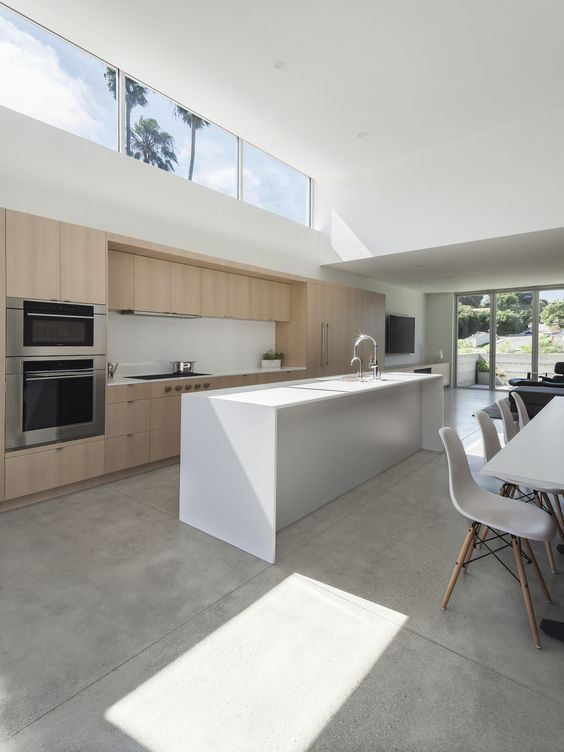 a minimalist space with a kitchen and dining room, with minimal furniture, a glazed wall and a clerestory window for more light here