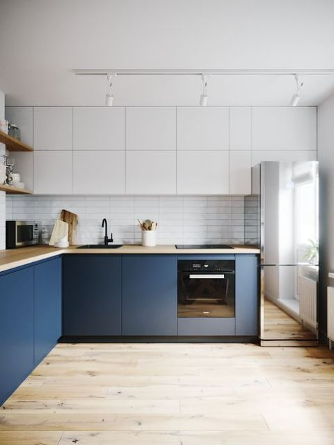 a minimalist two-tone kitchen with butcherblock countertops and a mirror fridge is a very edgy solution