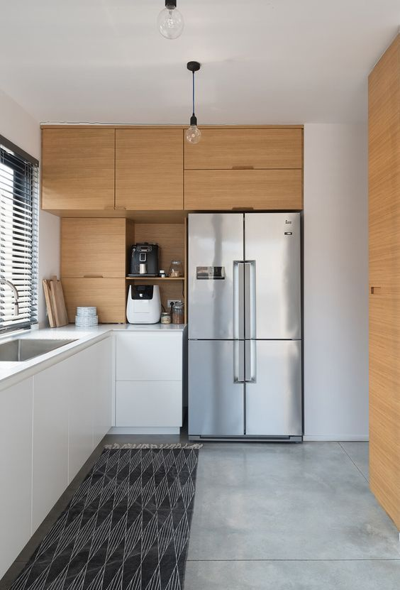 a minimalist two-tone kitchen with sleek cabinetry, white stone countertops and a printed rug is very stylish