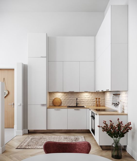 a minimalist white L shaped kitchen with a brick backsplash, butcherblock countertops and built in lights