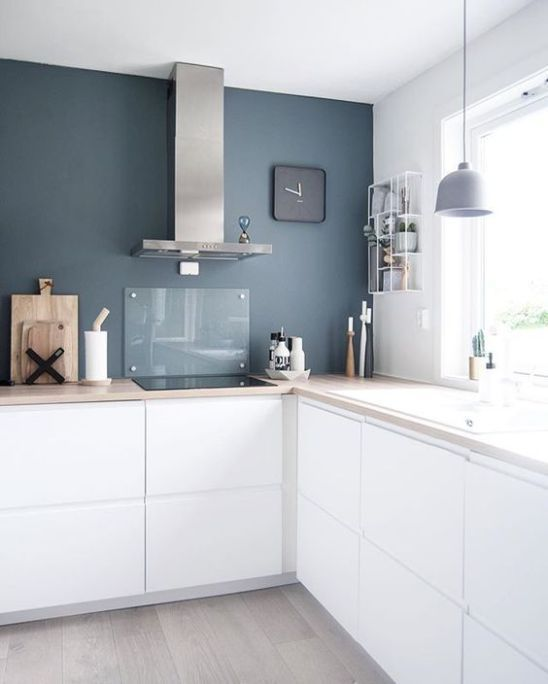a minimalist white L shaped kitchen with butcherblock countertops, a glass backsplash and a pendant lamp