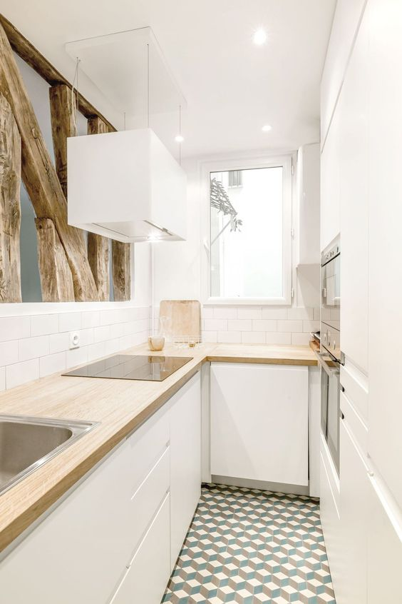 a minimalist white L shaped kitchen with butcherblock countertops and wooden beams looks very cool