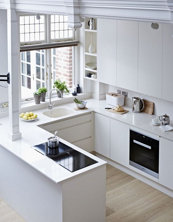 a minimalist white U-shaped kitchen with matching countertops and a backsplash, with built-in appliances