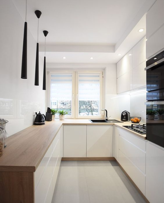 a minimalist white kitchen with butcherblock countertops, a white backsplash and catchy black pendant lamps