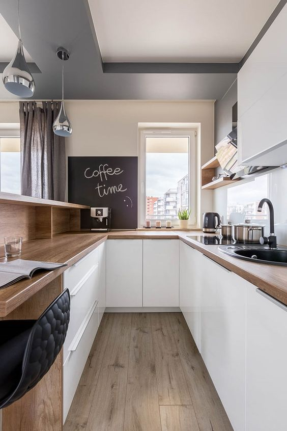a minimalist white kitchen with butcherblock countertops, a white glass backsplash and a chalkboard plus an office space