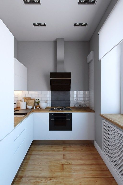 a minimalist white kitchen with butcherblock countertops, a white tile backsplash and built-in appliances