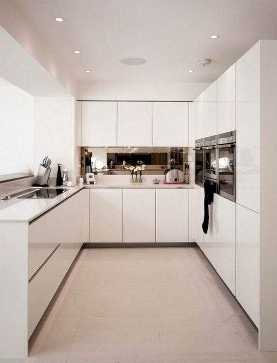 a minimalist white kitchen with white countertops and shiny staineless steel appliances is a very stylish idea