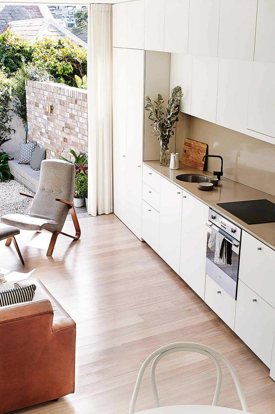 a minimalist white one wall kitchen, a tan backsplash and coutnertops and black fixtures is an elegant idea for an open space
