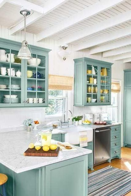 a mint L shaped kitchen with a white stone countertop, woven shades and touches of yellow is very chic