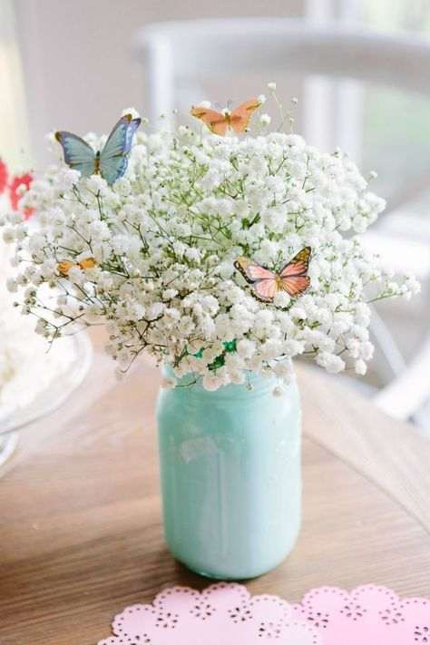 a mint colored jar with baby's breath and colorful paper butterflies is a chic and lovely idea for spring