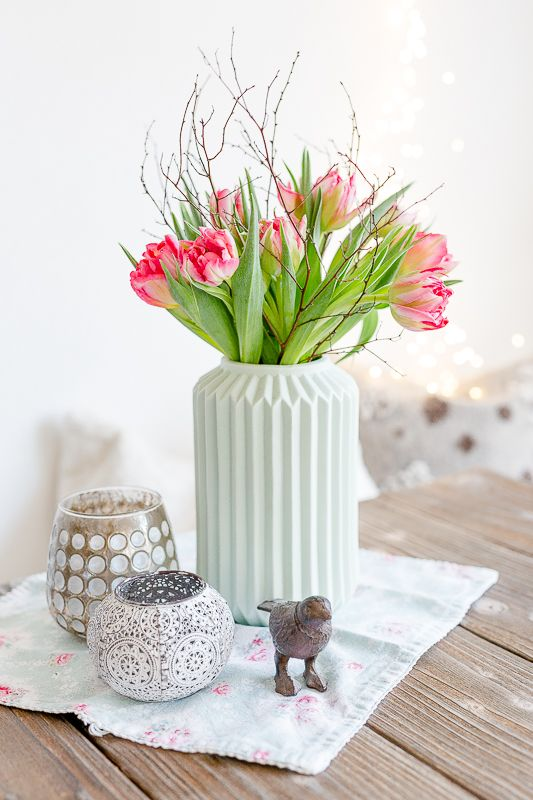 a mint green ribbed vase with pink tulips and twigs is a very chic and lovely decoration or centerpiece for spring