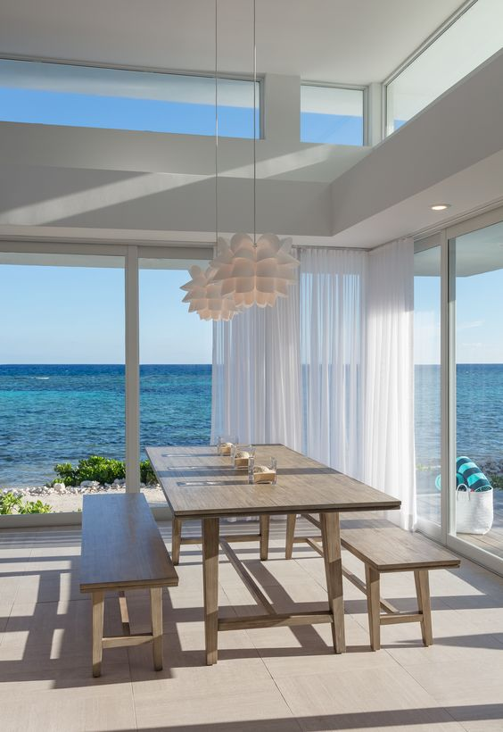 a modern beach house in white, with wooden furniture, pendant lamps and glazed walls plus clerestory windows