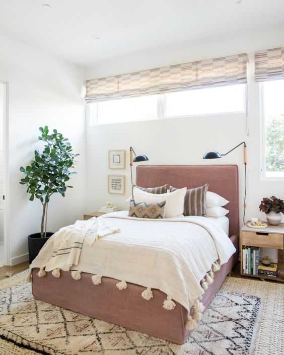 a modern bedroom with a window and a clerestory window, a mauve bed and sconces plus a potted plant