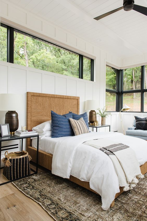 a modern farmhouse bedroom with a blue bench with pillows, a large window and an additional clerestory one