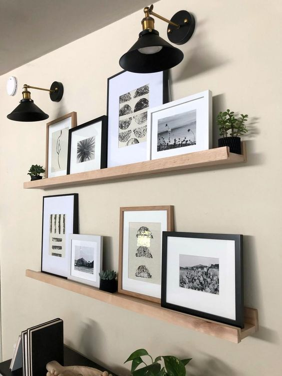 a modern farmhouse gallery wall with light stained wooden ledges, black and white artworks, potted greenery and elegant black sconces