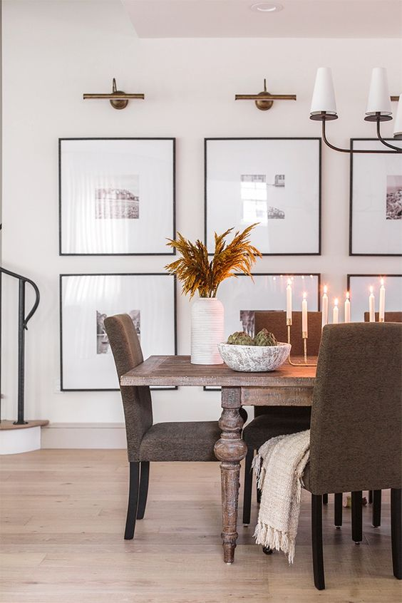a modern gallery wall with black and white photos and with matching black frames is a very cool and stylish idea