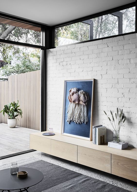 a modern living room with a white brick wall, a glazed wall and clerestory windows that fill the space with more light