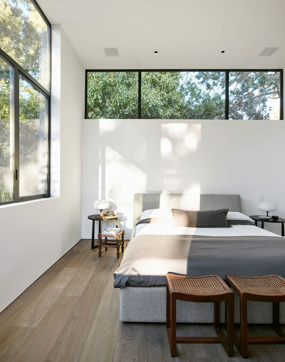 a modern neutral bedroom with contemporary furniture, a large window and a clerestory window over the bed is super chic