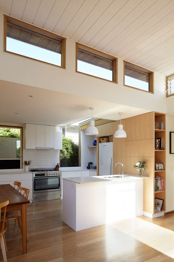 a modern neutral space with white and blonde wood furniture, usual and clerestory windows for more light inside