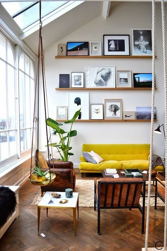 a modern space with a gallery wall on stained wooden ledges, with black and white and colorful artworks that is located rather high