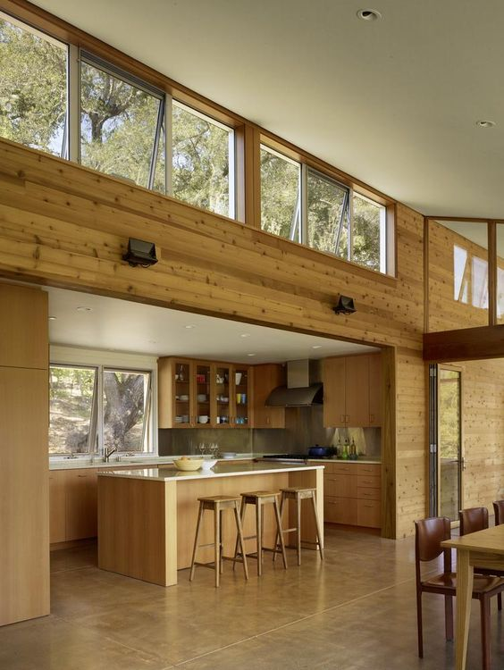 a modern tropical space with clerestory and usual windows, with wood cladding the walls and wooden furniture