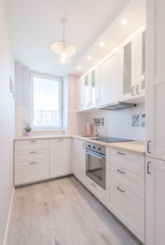 a modern white L shaped kitchen with a white tile backsplash and light stained butcherblock countertops
