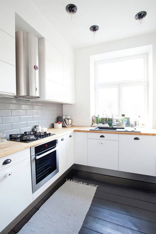 a modern white L-shaped kitchen with butcherblock countertops and a grey tile backsplash plus a black floor