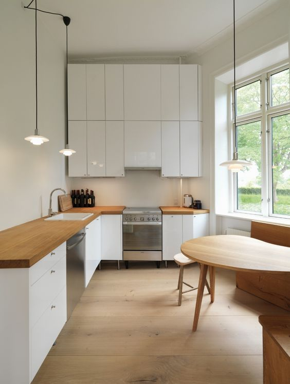 a modern white L-shaped kitchen with butcherblock countertops and a sleek white backsplash plus a dining space by the window
