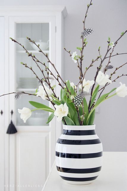 a monochromatic Easter centerpiece of a striped vase, whiet tulips, willow and feathers attached