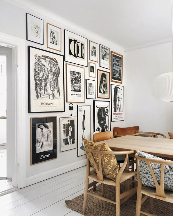 a monochromatic gallery wall with thin black and blonde wood frames and black and white artworks is a stylish idea