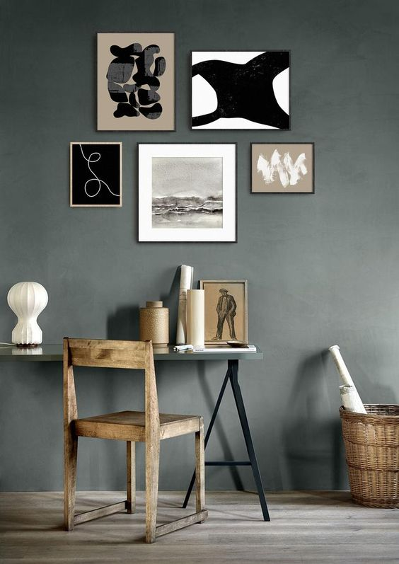 a moody gallery wall with thin blonde wood and black frames and black and white artworks for a modern space