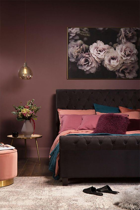 a moody mauve bedroom with a dark brown upholstered bed, pink, peachy and teal bedding, touches of gold and a floral artwork
