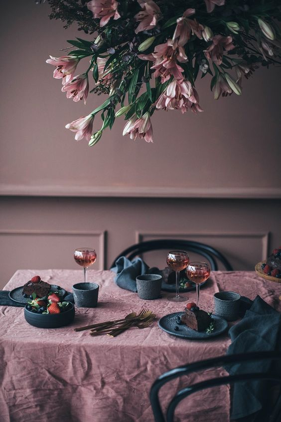 a moody mauve dining room with black chairs, mauve and black linens and plates is a very refined idea