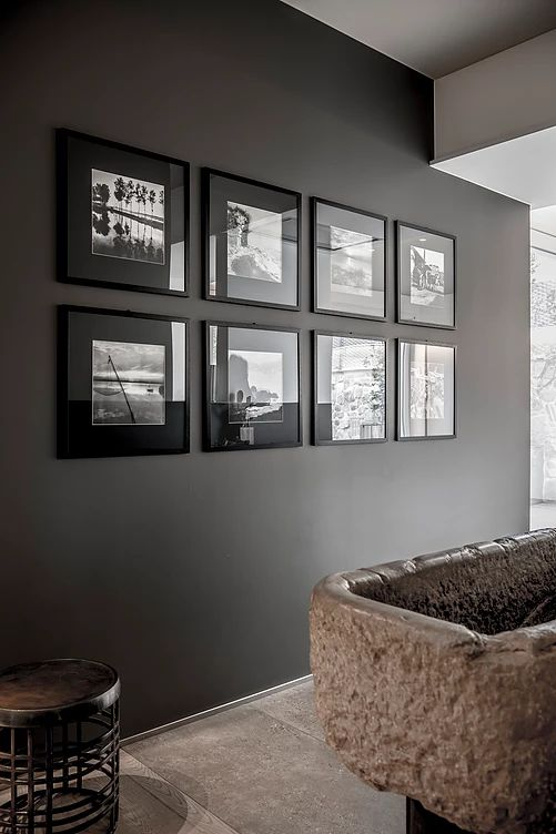 a moody symmetrical black and white gallery wall with matching black frames and black and white pics for a moody space